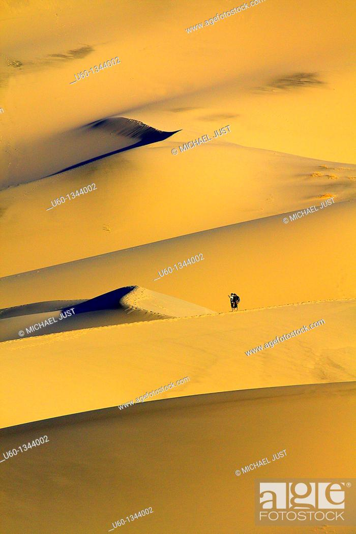 Stock Photo: Hikers make their way up Eureka Dunes at Death Valley National Park.