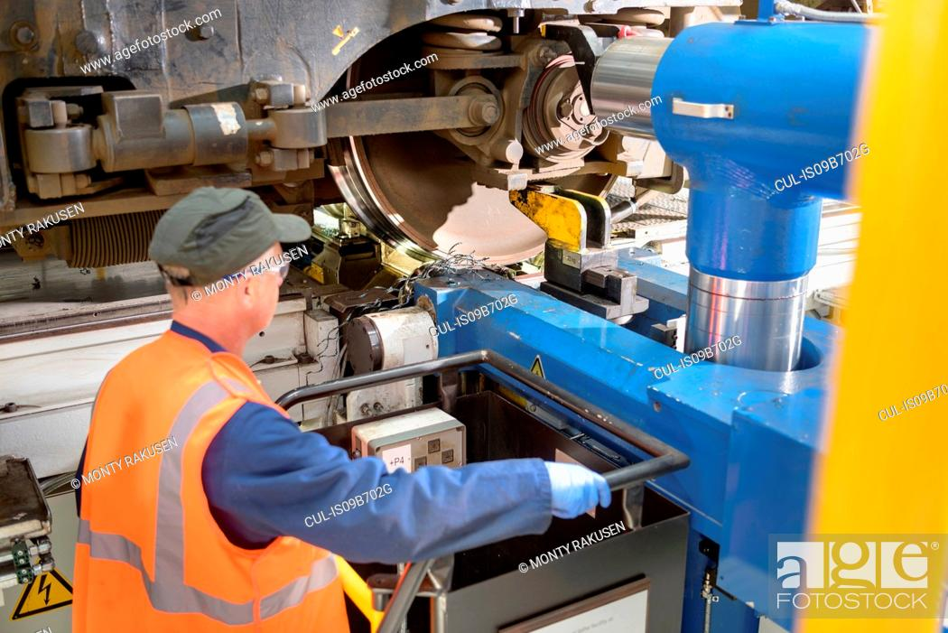Stock Photo: Engineer with locomotive wheel lathe in train works.