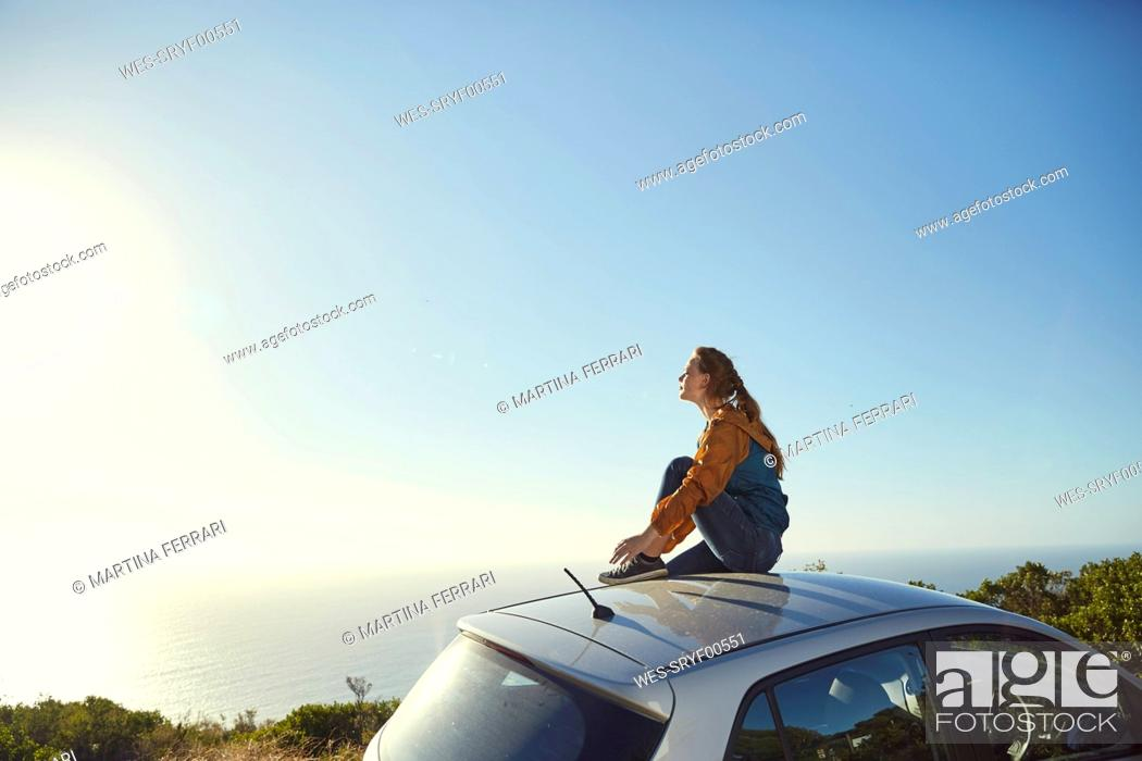 Stock Photo: South Africa, Cape Town, Signal Hill, young woman sitting on top of car enjoying the view to the sea.