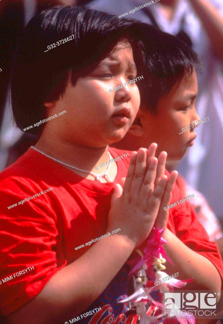 """Stock Photo: girl, Buddhist, """"""""praying"""""""", with flower offering, Thailand."""
