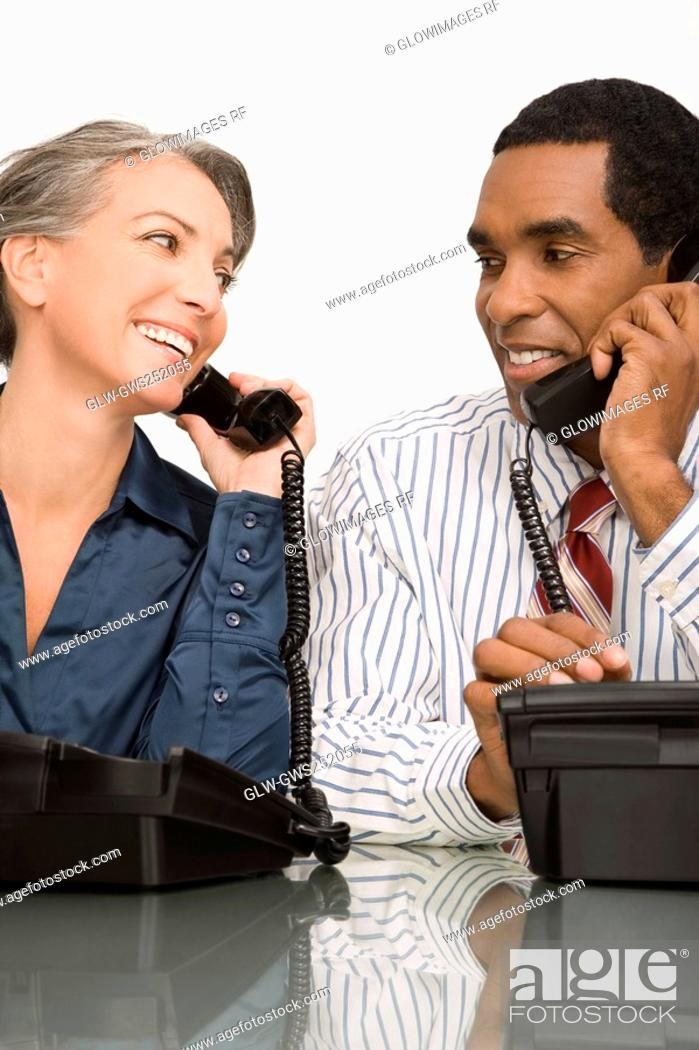Stock Photo: Businessman and a businesswoman talking on landline phones.