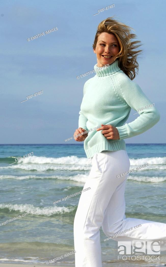 Stock Photo: Woman in turquoise pullover at the sea.