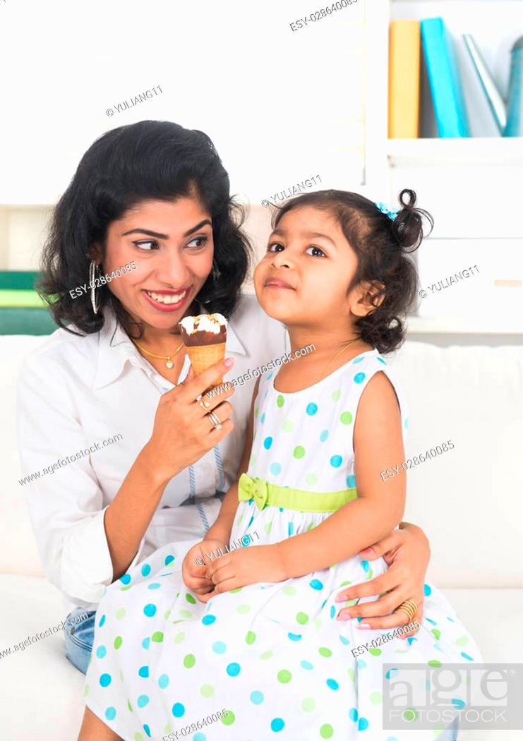 indian mother and child enjoying ice cream indoor, Stock
