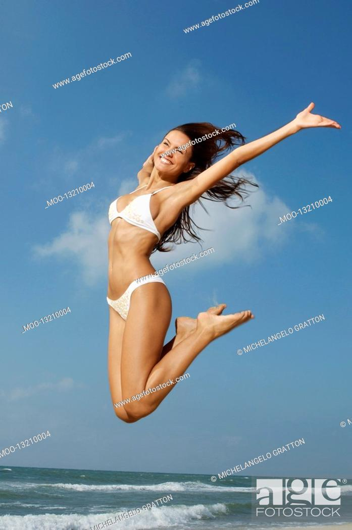 Stock Photo: Woman jumping on beach mid-air.
