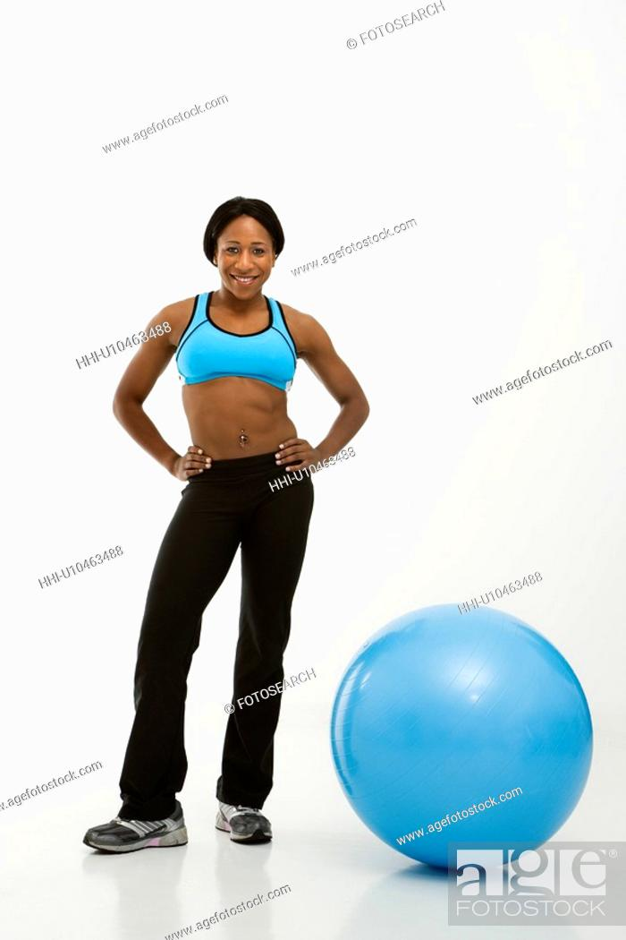 Stock Photo: African American young adult woman smiling at viewer with hands on hips next to exercise ball.