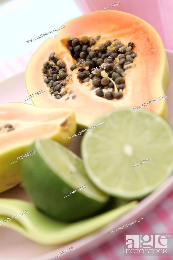 Stock Photo: Sliced pawpaw tree fruit and limes.
