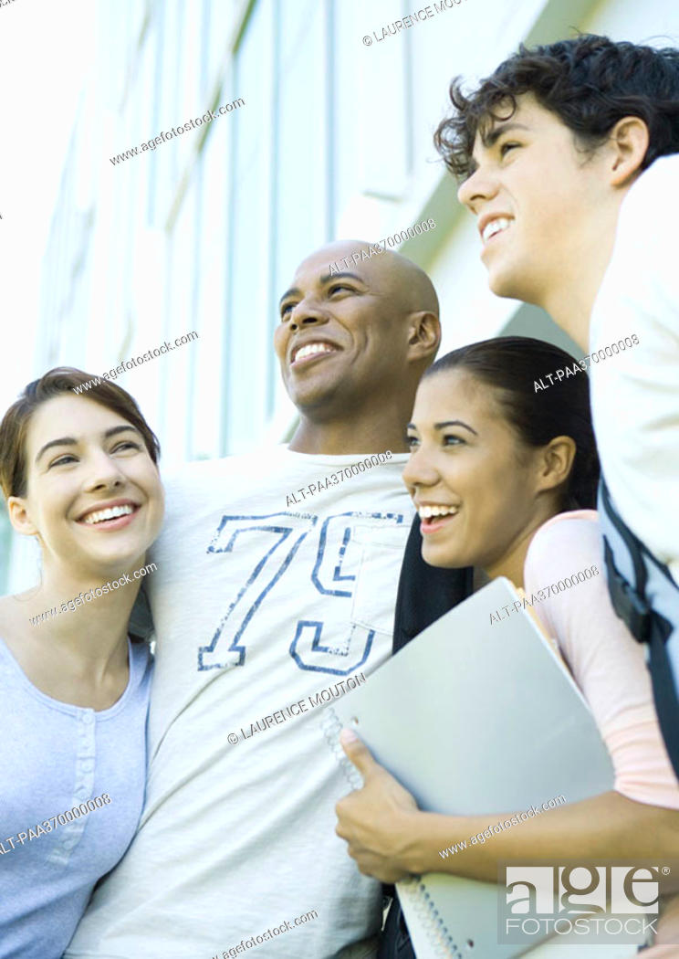 Stock Photo: Group of college students standing close together, smiling.