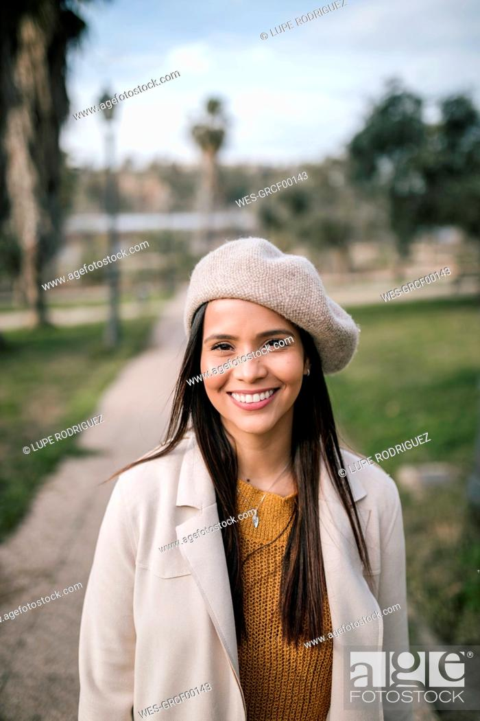 Stock Photo: Portrait of smiling young woman with beret in a park.