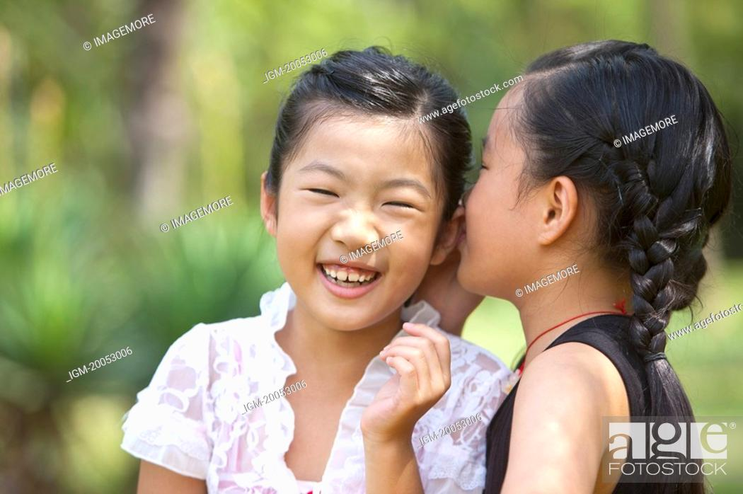 Stock Photo: Two girls whispering and smiling happily.