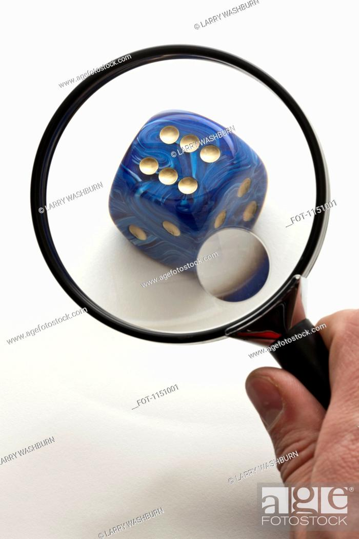 Stock Photo: A hand holding a magnifying glass up to a dice.