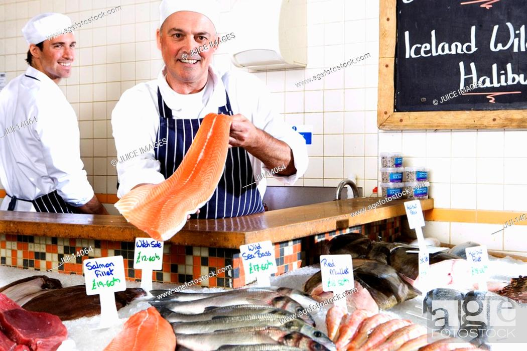 Stock Photo: Fishmonger behind counter holding up fillet of fish, smiling, portrait.