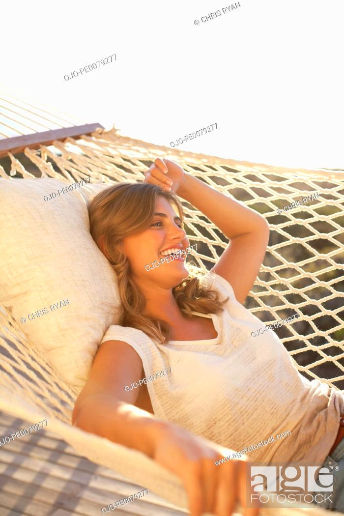 Stock Photo: Smiling woman laying in hammock.