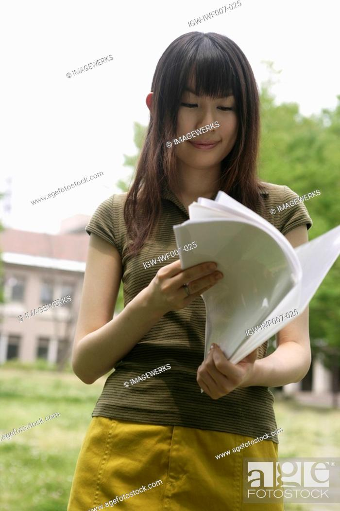Stock Photo: A young woman smiles as she goes through the files and papers.