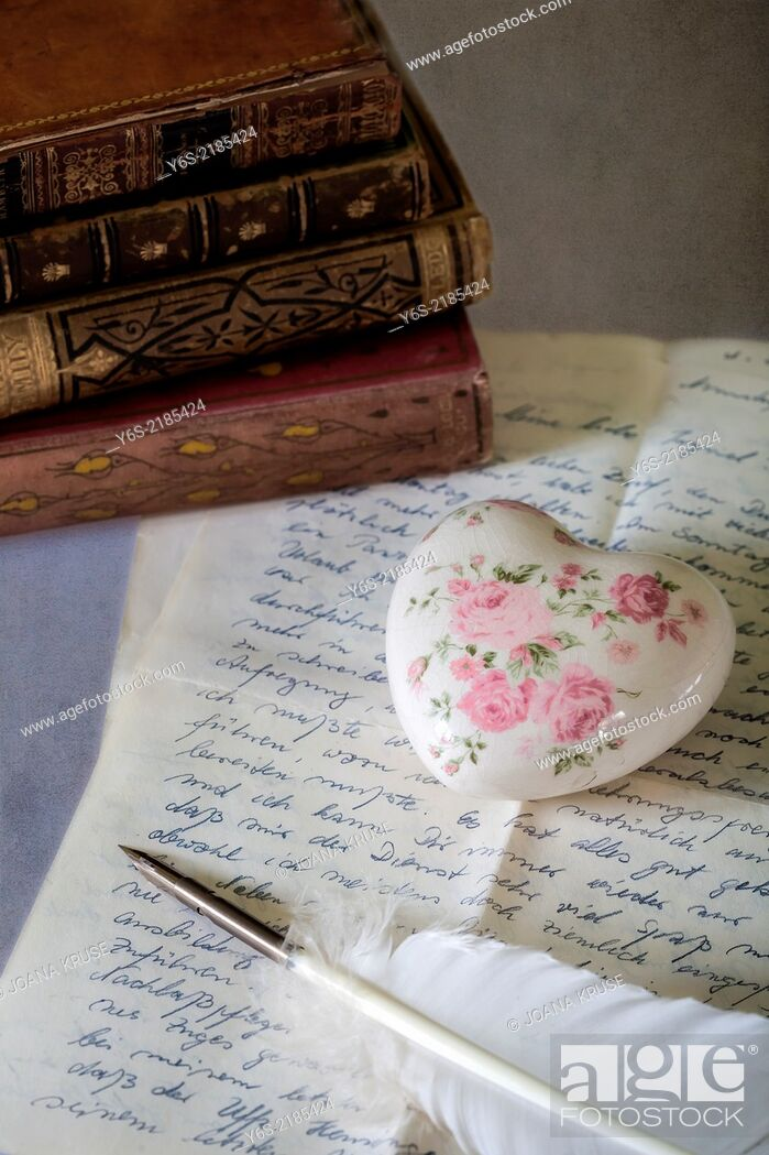 Stock Photo: a quill on an old letter with books.