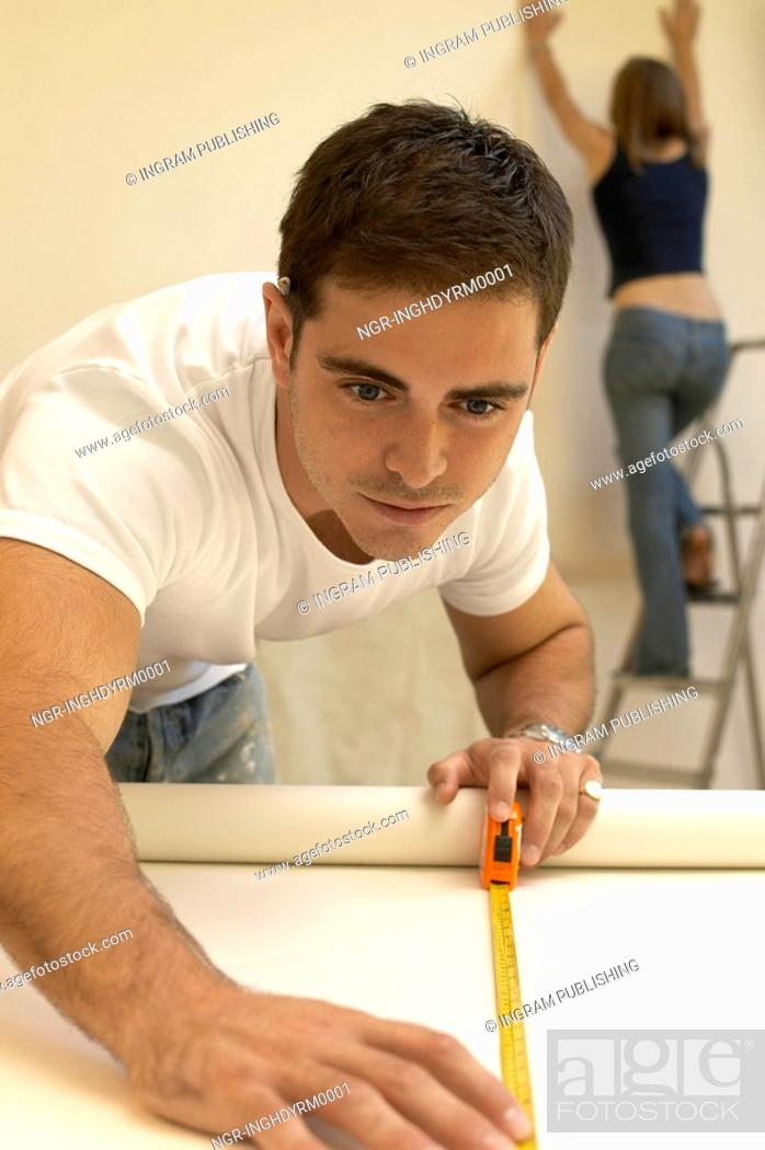 Stock Photo: Close-up of a young man measuring a roll of wallpaper with a woman on a step ladder behind him.