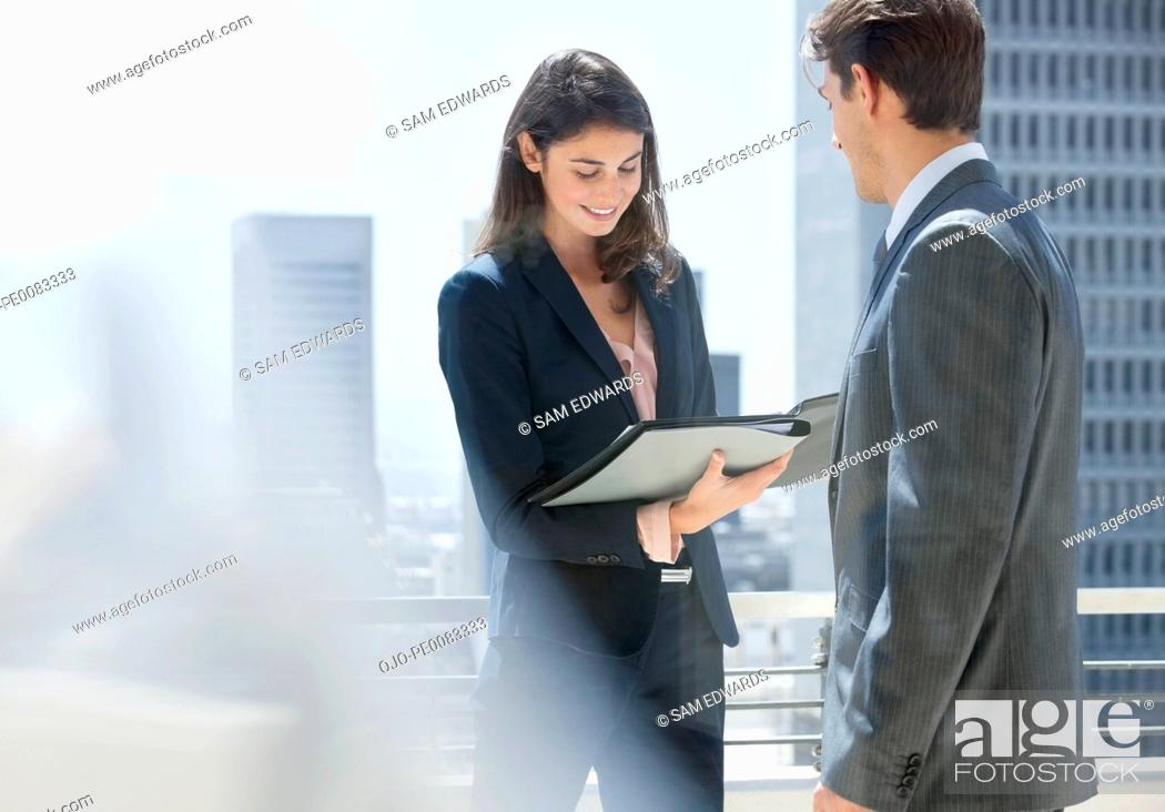 Stock Photo: Businessman and businesswoman reviewing paperwork on urban balcony.