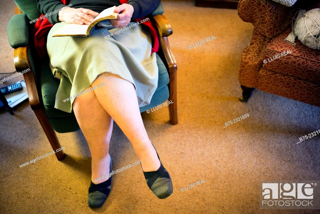 Stock Photo: Closeup of an elderly lady legs resting sitting in an armchair and reading a book on a cottage in Yorkshire, England, UK.