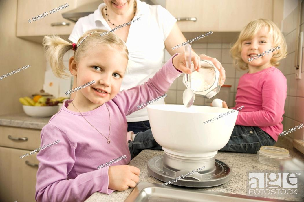 Stock Photo: Mother and daughter preparing cake in kitchen.