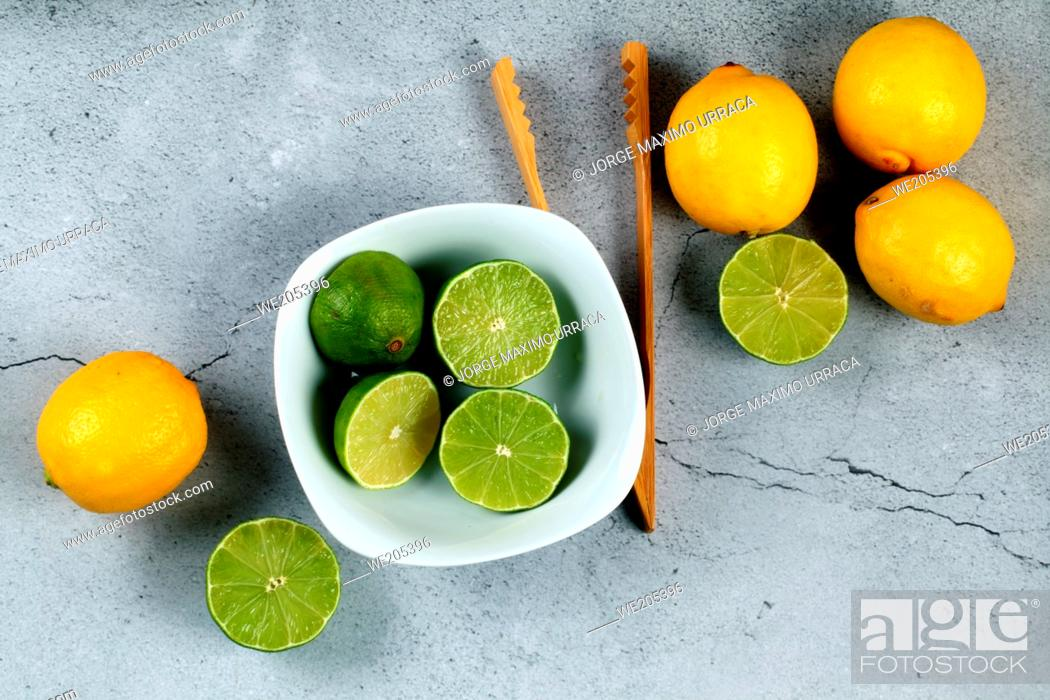 Photo de stock: Limes in white bowl with lemons and wooden kitchen utensil on stone background.