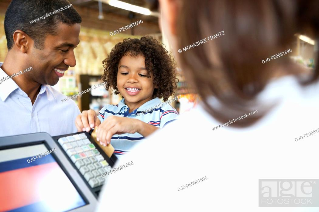 Stock Photo: Boy running father's credit card at supermarket.