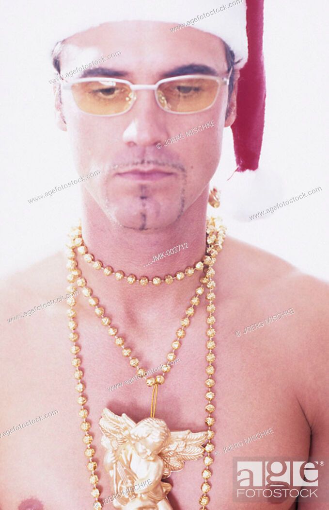 Stock Photo: A young man, 20-25 25-30 30-35 years old, stripped to the waist, wearing a Santa Claus cap, a golden necklace and sunglasses.