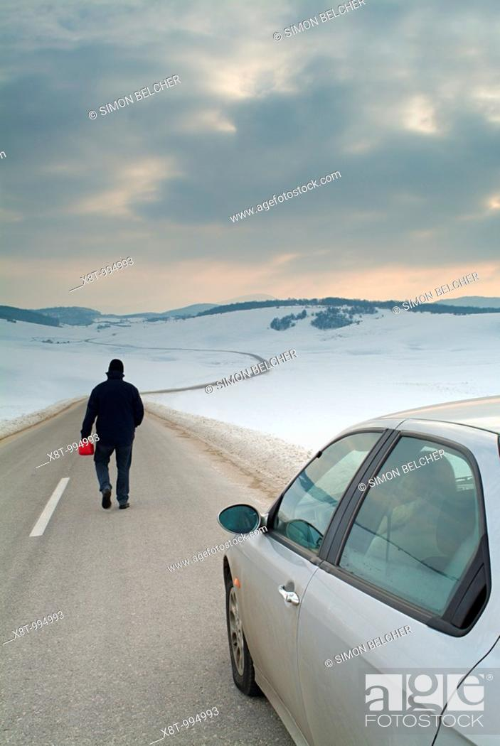 Stock Photo: Man Starts the Long Walk Along an Isolated Country Road in Winter to Find Fuel for His Broken Down Car.