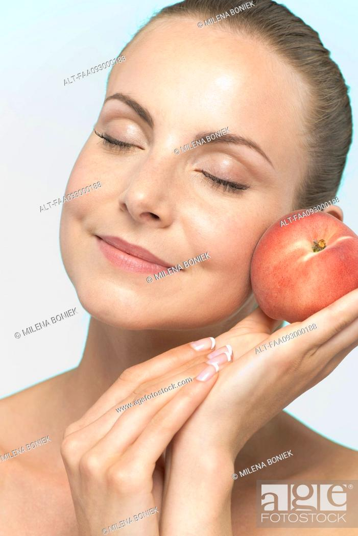 Stock Photo: Young woman holding peach to cheek.