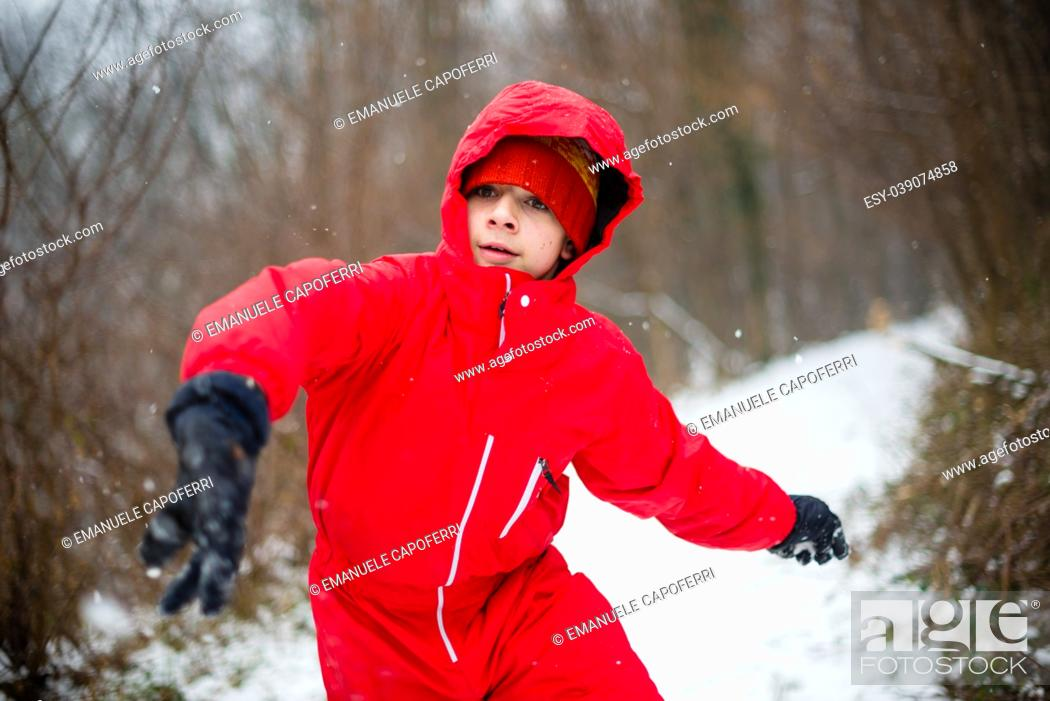 Stock Photo: portrait of teenager with red jacket and hat in the snowy forest, throws a snowball.
