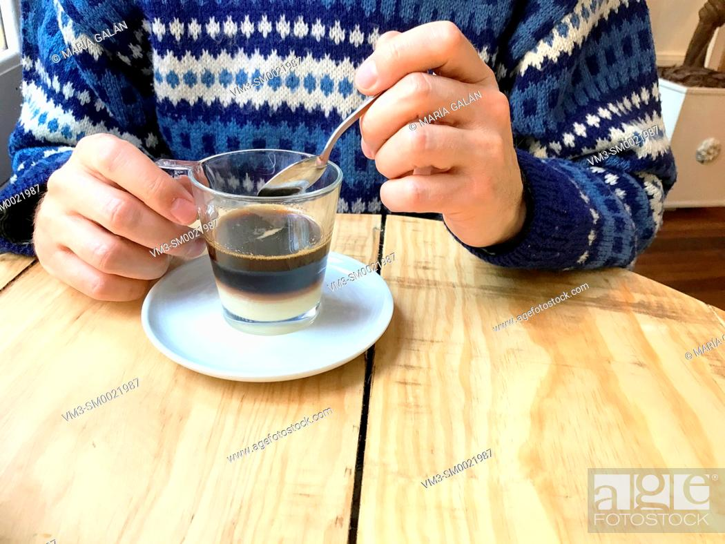 Stock Photo: Man's hand having bombon coffee in a cafe. Close view.