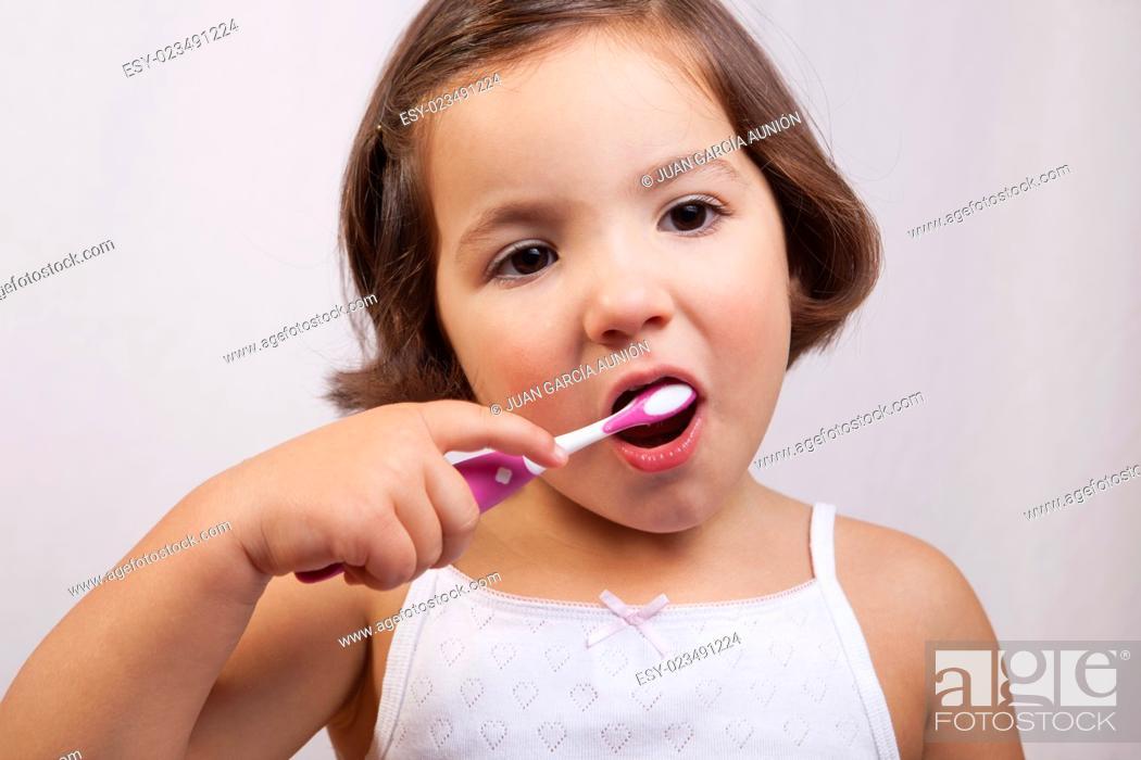 Imagen: Little brown eye girl brushing her teeth. Isolated over white background.