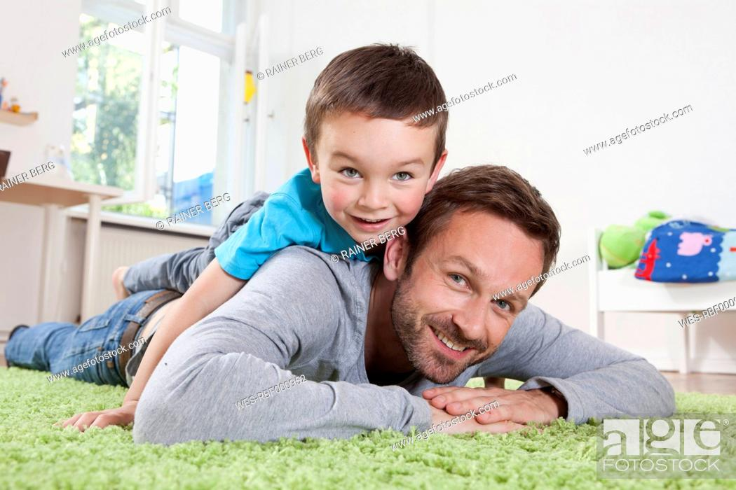 Stock Photo: Germany, Berlin, Father and son having fun at home, smiling.