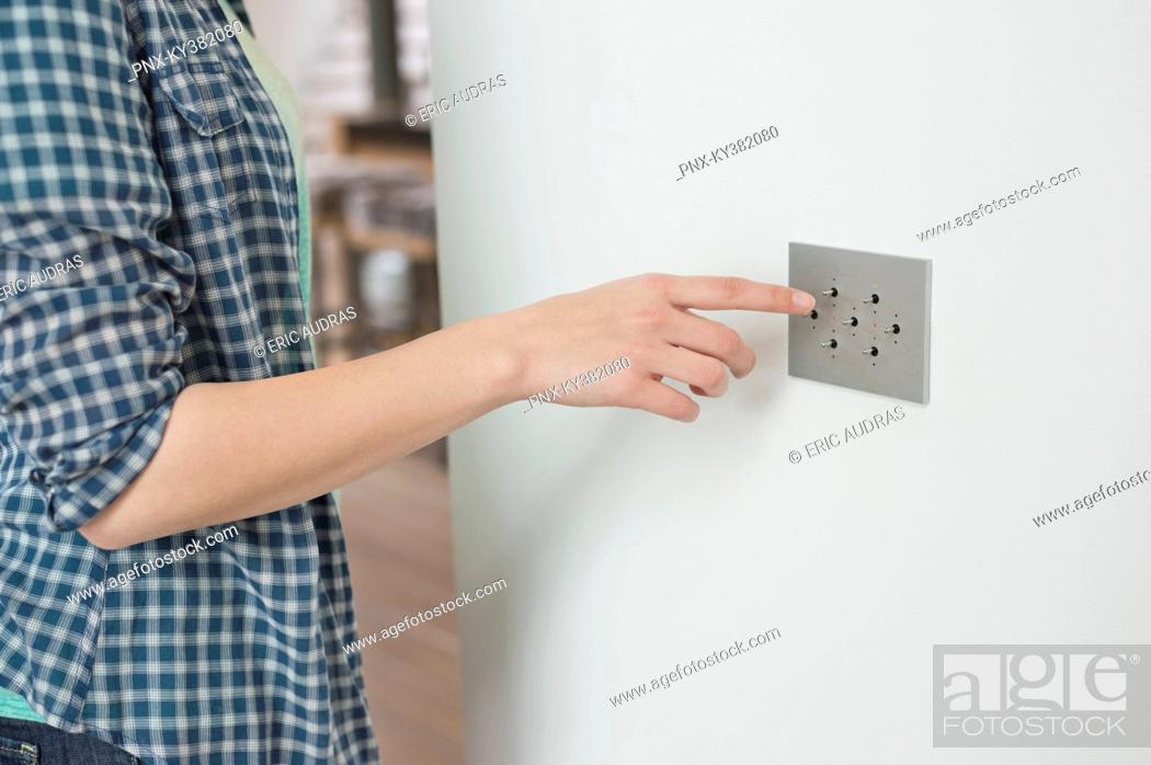 Stock Photo: Woman pressing light switch on a wall.