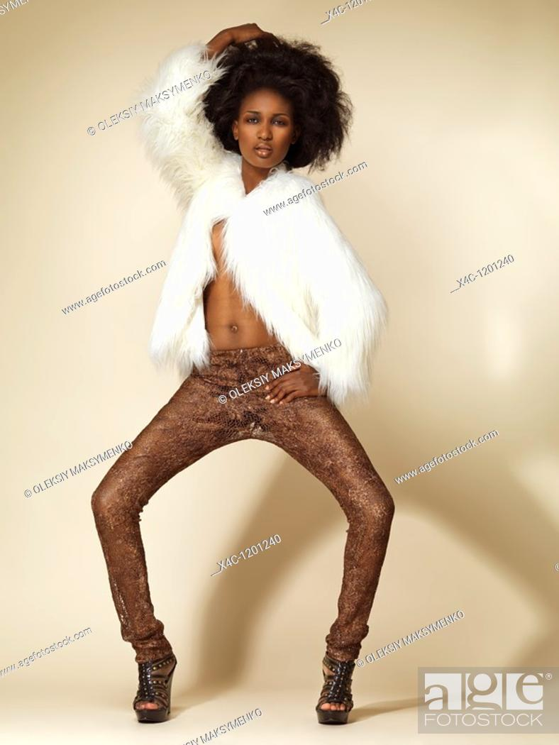 Stock Photo: High fashion photo of a young woman wearing a white fur jacket.