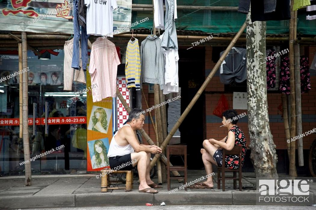 Stock Photo: A woman and a man sitting outside his home with his clothes on the street. Shanghai, China.