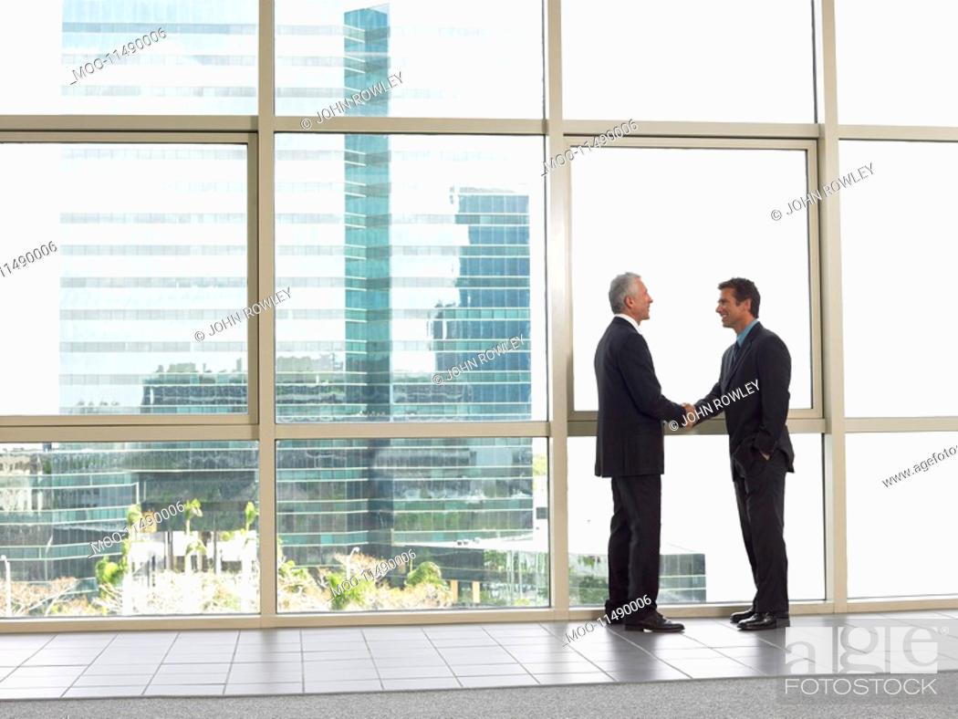 Stock Photo: Businessmen shaking hands in office building.