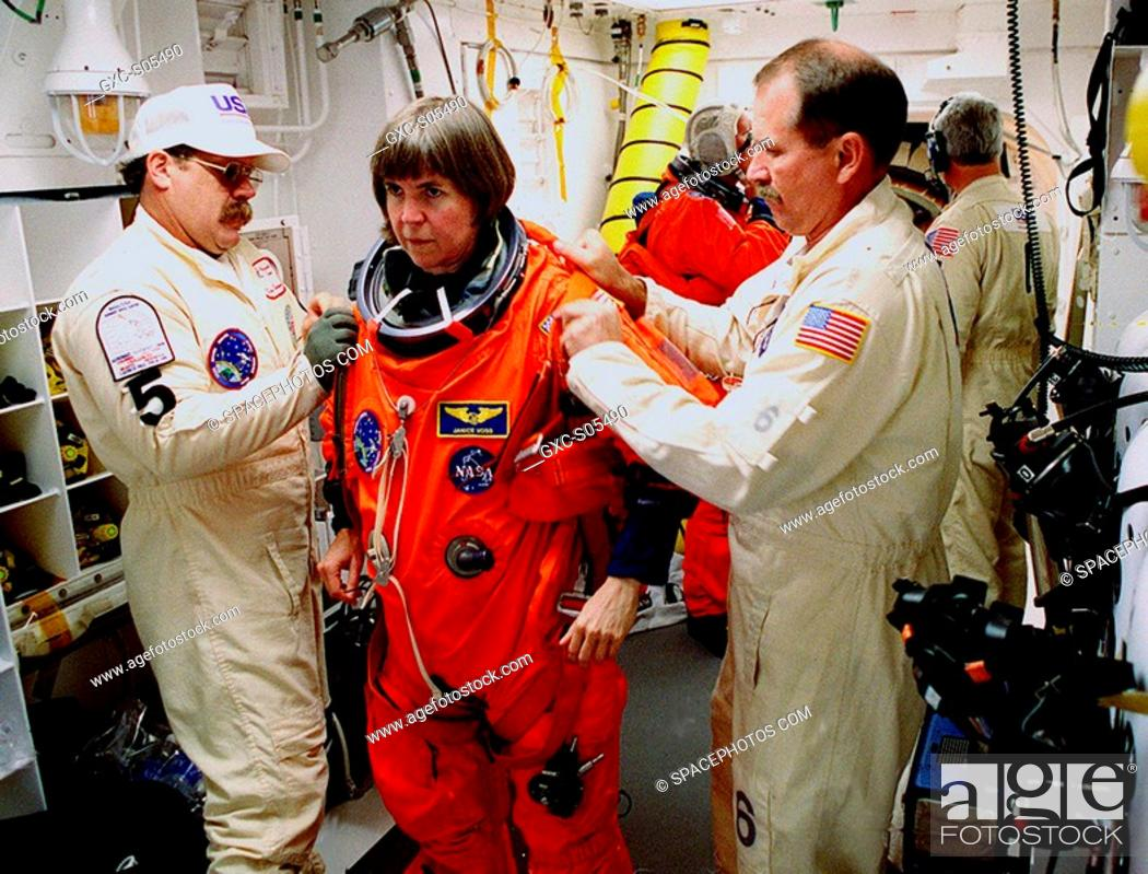 Stock Photo: 02/11/2000 --- Before entering the orbiter Endeavour, STS-99 Mission Specialist Janice Voss is helped by Travis Thompson and Jack Burritt.