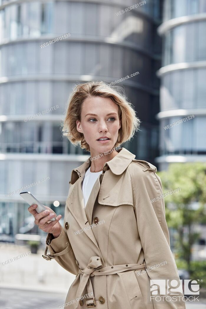 Stock Photo: Germany, Duesseldorf, portrait of blond young businesswoman with smartphone wearing beige trenchcoat.