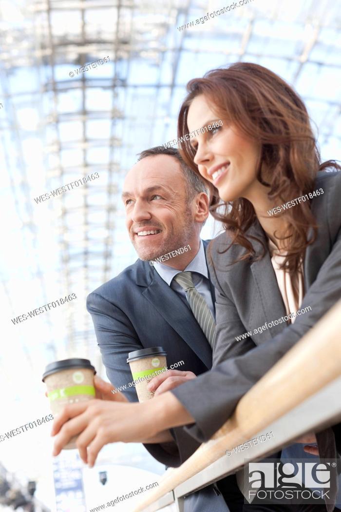 Stock Photo: Germany, Leipzig, Business people having coffee, smiling.
