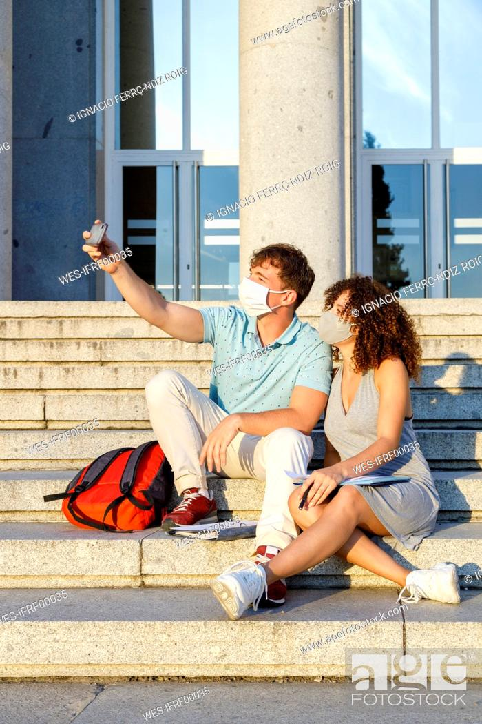 Stock Photo: Male friend taking selfie with university student wearing protective mask while sitting on staircase in city.
