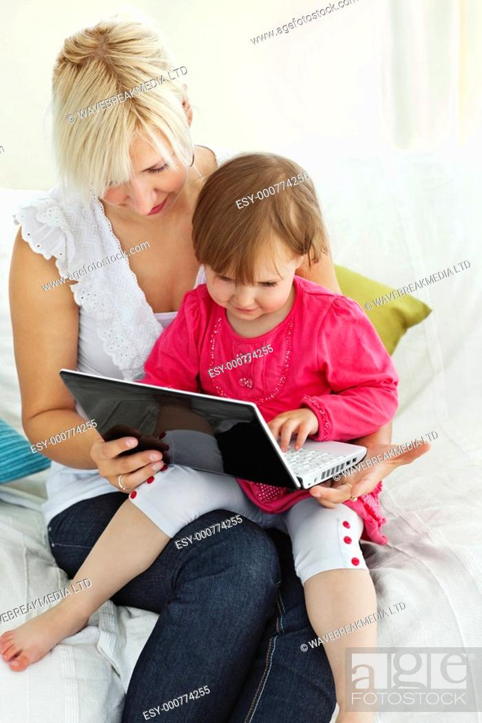 Stock Photo: Mother and daughter having fun with a laptop in the living-room at home.