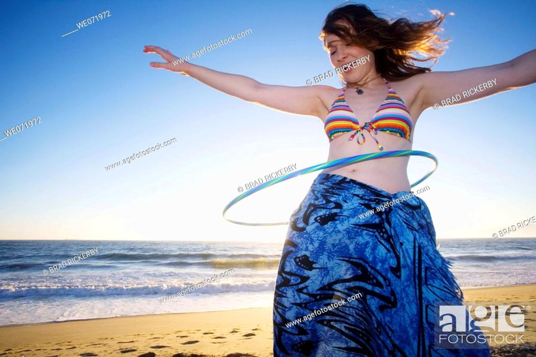Stock Photo: 20 year old woman does the hula hoop on the Pacific ocean beach in Los Angeles, California, USA.
