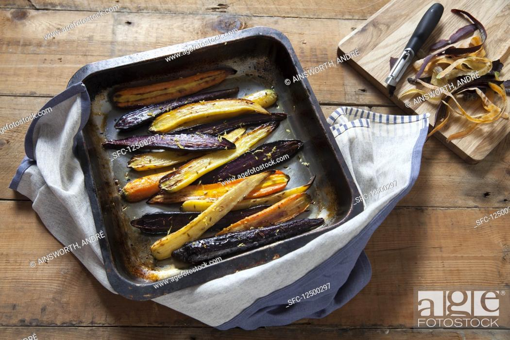 Photo de stock: Roasted heritage carrots with lemon and cumin in a baking tray.