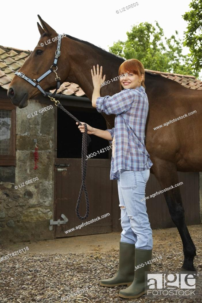 Stock Photo: Woman with horse outside stable portrait.