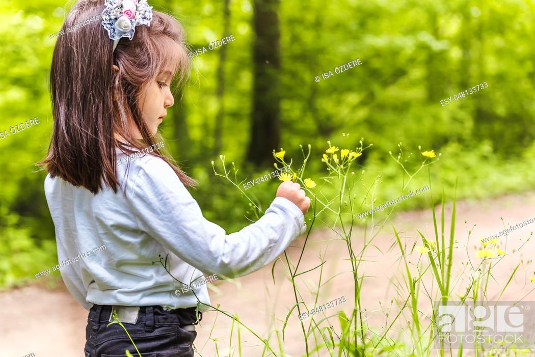Photo de stock: Adorable four years old cute little girl picks wild flower at meadow in a sunny day.