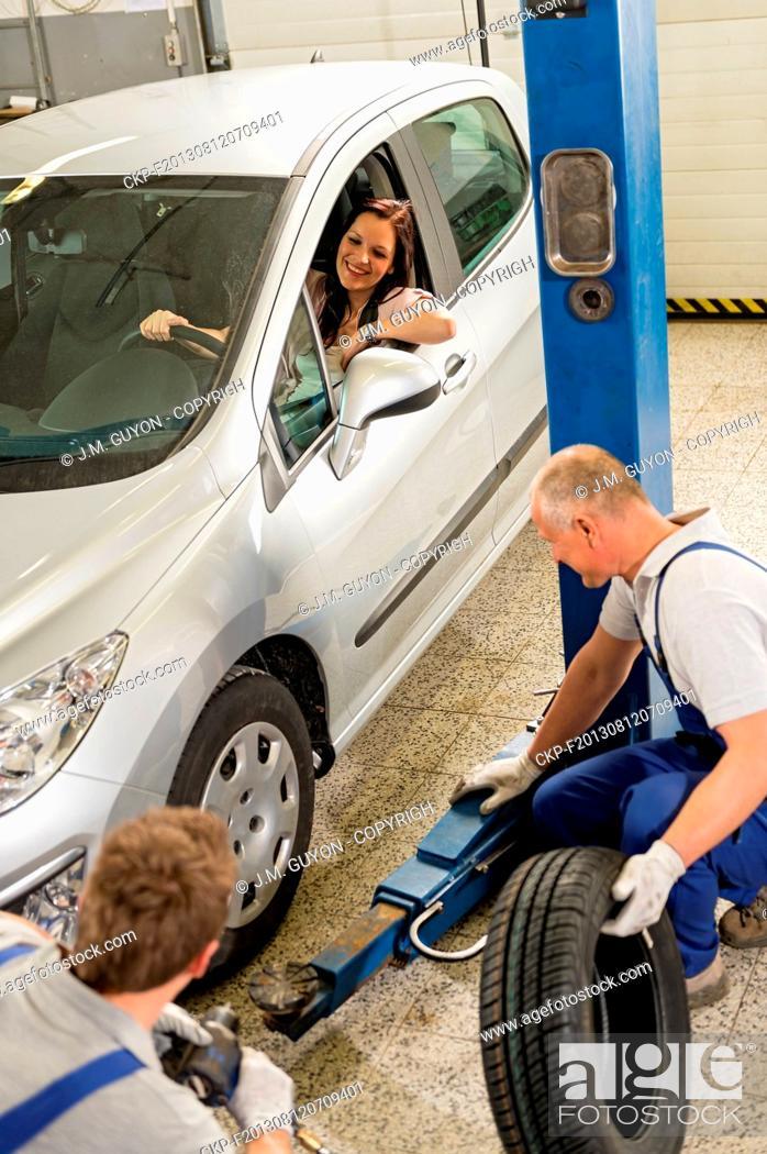 Imagen: Caucasian car salesman changing tire in garage.