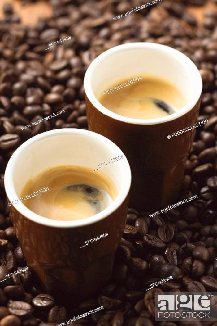 Stock Photo: Two espressos standing on coffee beans.