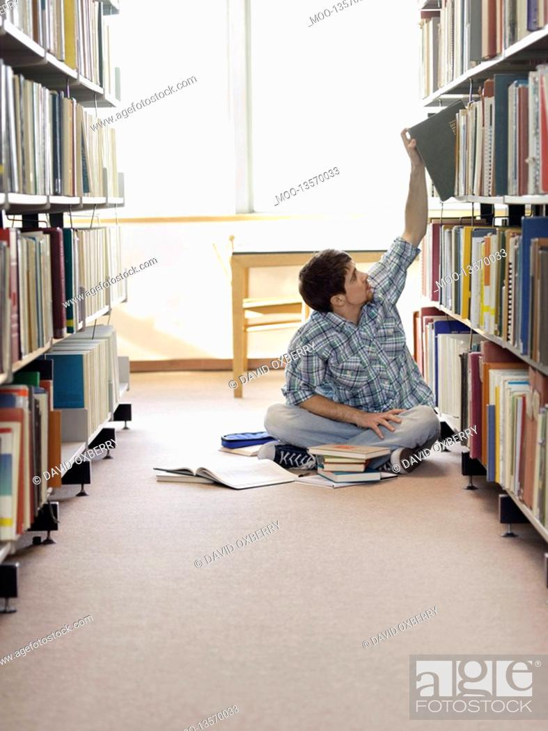Stock Photo: Student sitting on floor in library reaching for book.