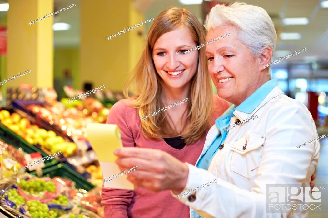 Stock Photo: Germany, Cologne, Women with list in supermarket.