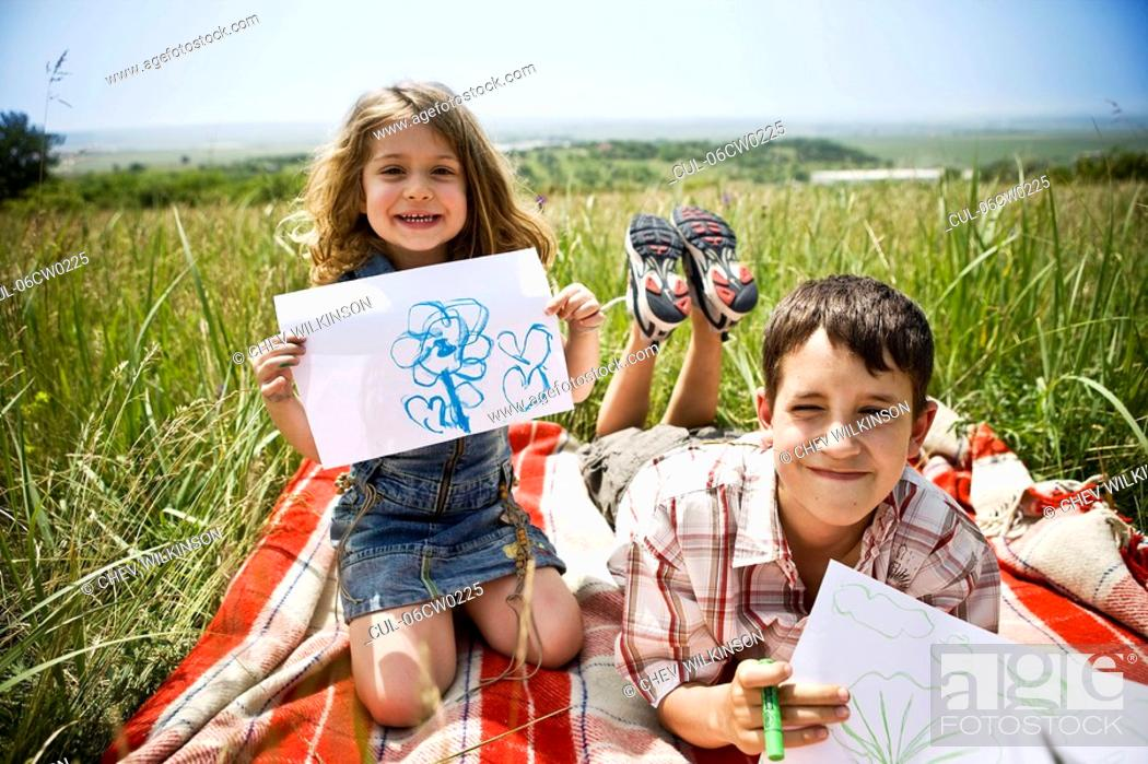 Stock Photo: Two children showing their drawings.