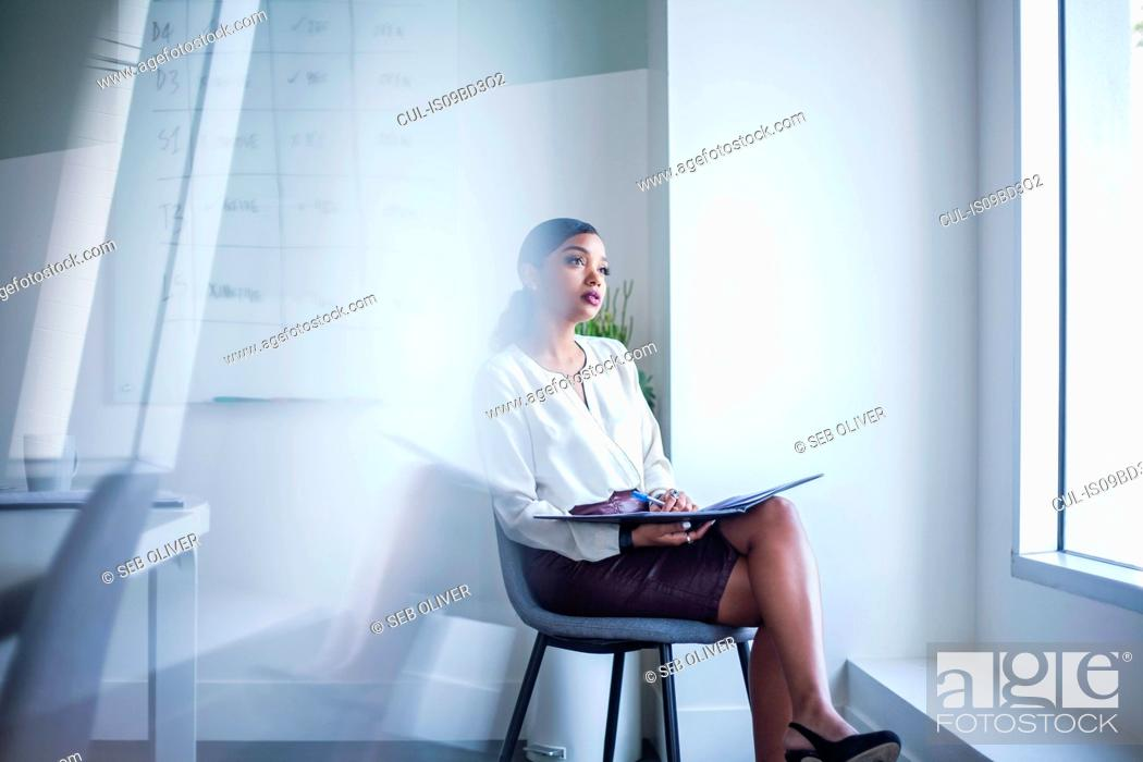 Stock Photo: Businesswoman sitting in office looking out of window.